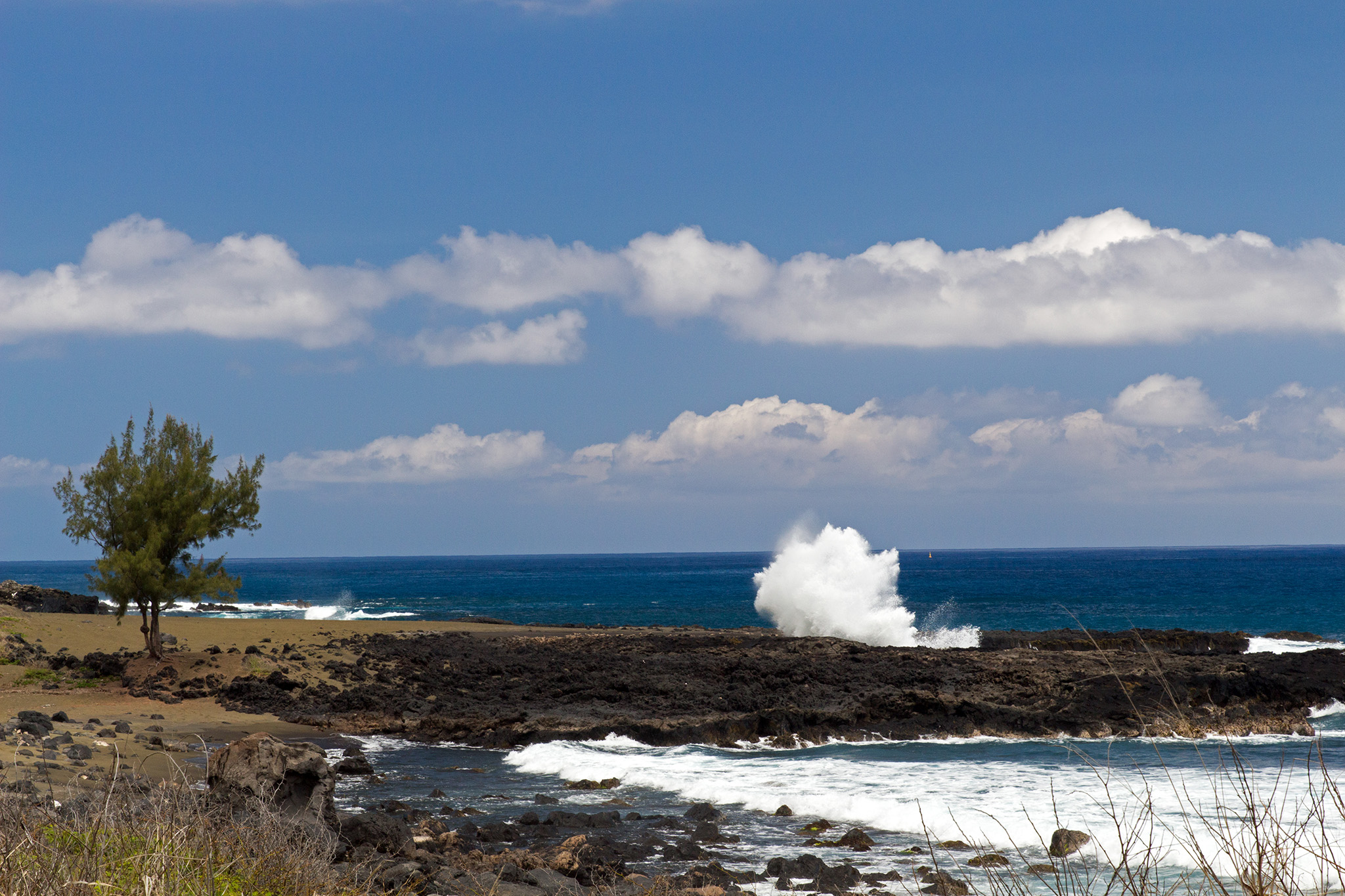 La Réunion - Gischt von der Brandung des Indischen Ozeans, die auf Lavagestein trifft.