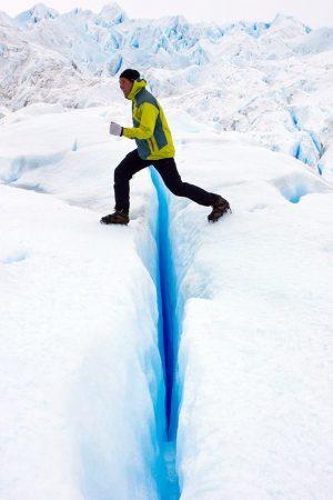 Gewagter Schritt über eine Gletscherspalte auf dem Perito Moreno in Patagonien, Argentinien